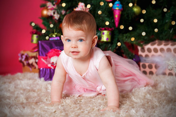 Beautiful baby girl playing under the christmas tree