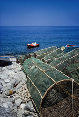 Italy, Calabria, wooden fishing boats and fish traps ashore