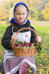 Маленькая девочка на осенней поляне, с корзиной рябины