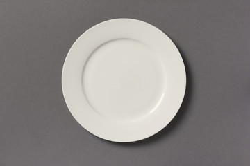 Top view of white empty plate on grey background