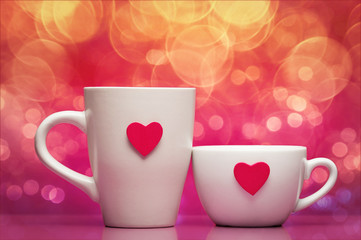 Cups with valentines day heart on pink background