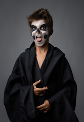 Teen with make-up of skull in black cloak showing tongue