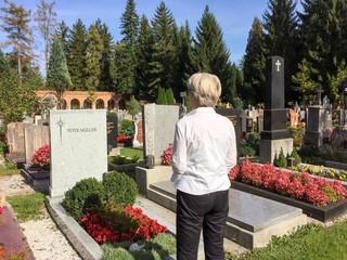 Ältere Frau steht an Grsb auf Friedhof