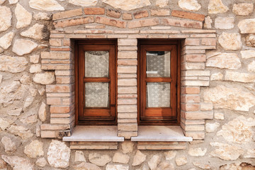 Old stone wall with two small windows in wooden frames