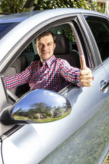 Happy young man with thumb up at the wheel