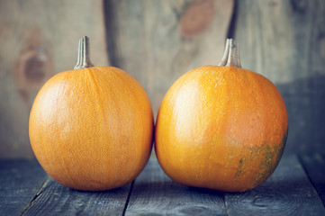Two pumpkins lie on wooden board
