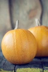 Pumpkins lie on wooden board