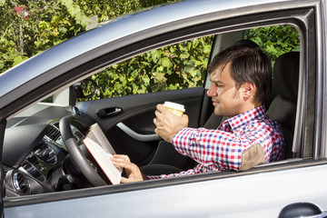 Young man reading and drinking coffee while driving