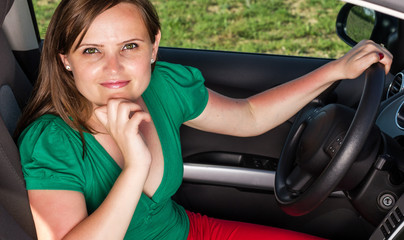 Attractive young woman sitting in her car