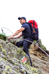 Young man hiking on difficult mountain trail with hanging cable