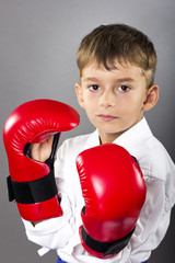 Portrait of a karate kid  wearing red gloves ready to fight