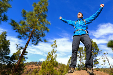 Man hiking reaching summit top cheering in forest
