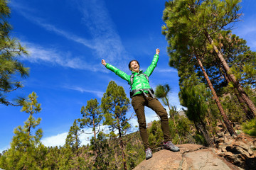Hiking woman reaching summit cheering in forest