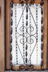 Ventana con marco de madera y forja y visillo de encaje