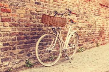 White bike near brick wall