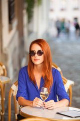 Redhead women with wine sitting in the cafe in Paris