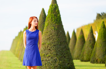 Beautiful redhead girl in Versailles park