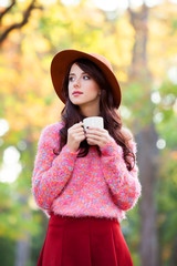 Brunette girl wtih cup of coffee in the autumn park.