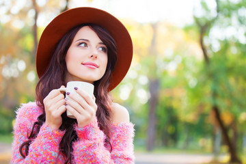 Brunette girl with cup of coffee in the autumn park.