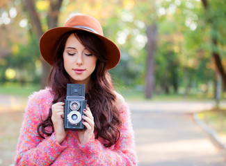 Beautiful redhead women with camera in autumn park.