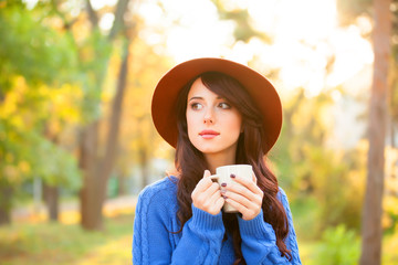 Brunette girl with cup in the park in sunset time