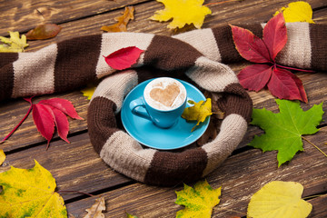 Autumn leafs, scarf and coffee cup on wooden table.