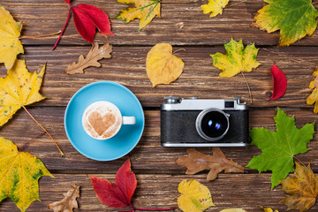 Autumn leafs, camera and coffee cup on wooden table.