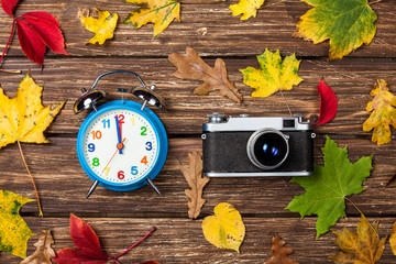 Autumn leafs, camera and alarm clock on wooden table.