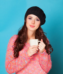 Brunette girl with cup on blue background
