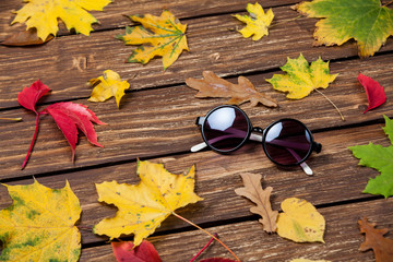 Sunglasses and leafs on wooden table.