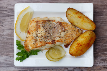 White fish with potato wedges on white plat, woodeen background