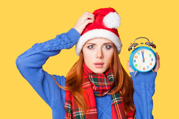 Redhead girl with alarm clock on yellow background.