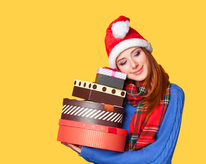 Redhead girl with gifts on yellow background