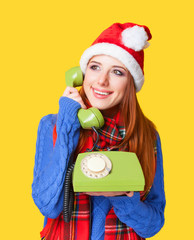 Beautiful redhead girl in christmas hat with telephone on yellow