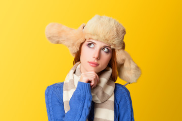 Redhead girl in hat on yellow background.