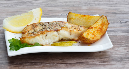 White fish with potato wedges on white plat, wooden background