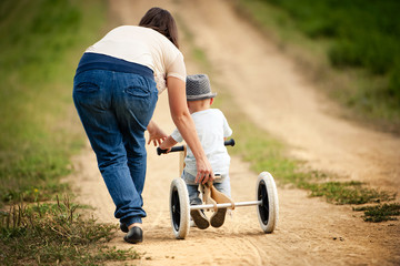 Mother with little boy on tricycle in nature