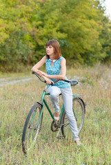 Beautiful girl with an old bicycle.