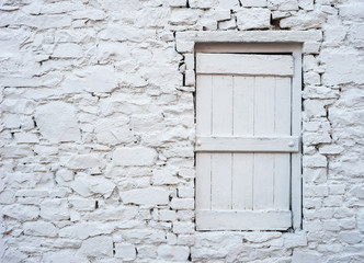 old white brick cottage with wooden window shutter