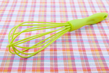 Whisk on a checkered tablecloth.