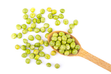 Green peas in a wooden spoon on a white background.