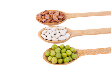 Beans and green peas in a spoon on a white background.