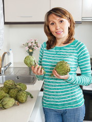 Smiling woman with artichoke