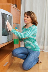 Adult housewife cleaning TV