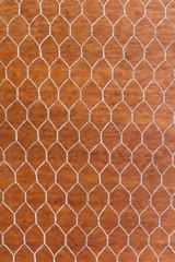 Wire mesh on orange wall