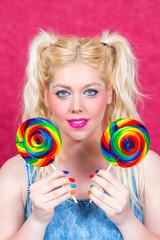 Blonde Frau mit blauen Augen und Lollipops in der Hand