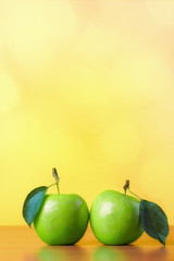 Two green apples with leafs on abstract yellow background