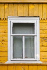 Russian rural house fragment, yellow wall and white window