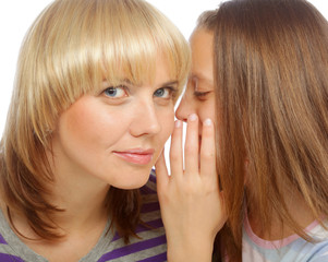 young girl whispering secrets in her mommy's ear
