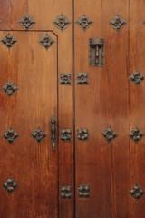 Puerta antigua decorada con detalles en hierro.